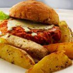 panino con hamburger di salmone e patatine in piatto